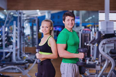 Portrait of  man and woman with dumbbells in hands  the gym. Stock Photo
