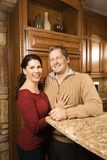 Portrait of man and woman in kitchen. Caucasian woman and Caucasian man with arms around each other leaning on kitchen counter and looking at viewer Royalty Free Stock Images