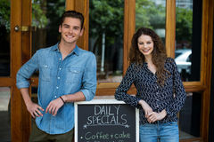 Portrait of man and woman leaning on menu board outside the cafe Stock Photography
