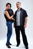 Portrait of man and woman with a small black dog. Studio shot Royalty Free Stock Image