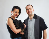Portrait of man and woman with a small black dog. Studio shot Stock Photos