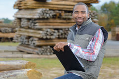Portrait man in woodyard with clipboard Stock Images