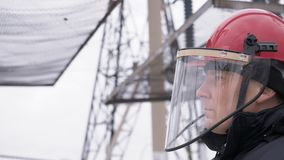 Portrait of man worker in warm uniform on electrical power plant at street. Portrait of worker in helmet, mask and warm uniform northern region. Electrical stock footage