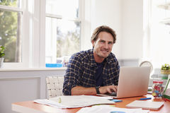 Portrait Of Man Working At Laptop In Home Office Stock Image