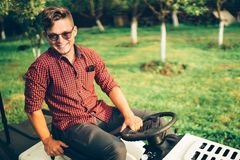 Portrait of man working on ride-on lawn mower tractor Stock Photo