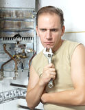 Portrait man with a wrench thinks of repair of a gas water heater Stock Images