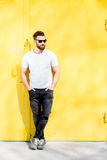 Portrait of a man on yellow background. Colorful portrait of a handsome man dressed in white t-shirt and jeans on the yellow background Royalty Free Stock Photo