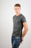 Portrait of a man. Young attractive stylish man in grey t-shirt standing. Royalty Free Stock Photography