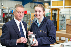 Portrait Of Manager And Apprentice Engineer Inspecting Component Stock Photos