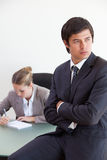Portrait of a manager posing while his colleague is working Royalty Free Stock Images