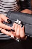 Portrait of manicured nails. With nail polish holding a wallet Stock Photography
