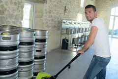 Portrait manufacturer carrying kegs in brewery Stock Photo