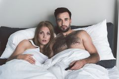 Shocked man and woman are interested in movie plot. Portrait of married young couple watching tv with excitement. They are lying in bed at home Royalty Free Stock Photo