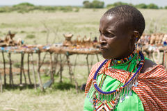 Portrait of Masai woman. In the background souvenir stalls Stock Photo