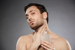 Portrait of masculine sexual man putting perfume aftershave on h. Is neck isolated over gray background royalty free stock images