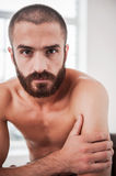 Portrait of masculinity. Confident young bearded man looking at camera while sitting indoors Royalty Free Stock Photography