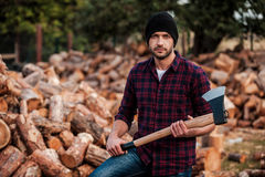 Portrait of masculinity. Confident young forester holding axe and looking at camera while standing outdoors Stock Photo