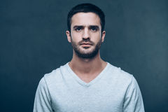 Portrait of masculinity. Handsome young man looking at camera while standing against grey background Stock Image