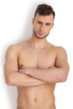 Portrait of masculinity. Thoughtful young muscular man looking at camera and keeping arms crossed while standing isolated on white background Royalty Free Stock Image