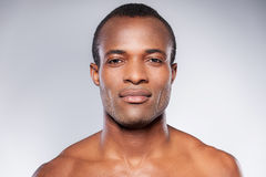 Portrait of masculinity. Portrait of young shirtless African man looking at camera while standing against grey background Stock Images