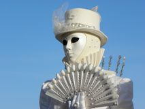 Portrait mask with fan, Carnival of Venice. White mask and outfit with a fan in one hand,gazing at the numerous tourists, Carnival of Venice, Italy Royalty Free Stock Photo