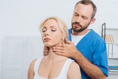 portrait of massage therapist massaging neck of young woman