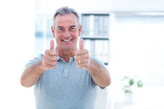 Portrait of masseur showing thumps sign Stock Photos