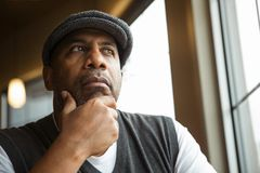 Portrait of a mature African American man in deep thought. Mature African American man sitting in a coffee shop Stock Photography