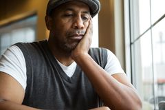 Portrait of a mature African American man in deep thought. Mature African American man sitting in a coffee shop Stock Images