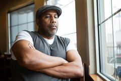 Portrait of a mature African American man in deep thought. Mature African American man sitting in a coffee shop Royalty Free Stock Photo