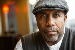 Portrait of a mature African American man in deep thought. Mature African American man sitting in a coffee shop Royalty Free Stock Image