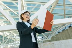 Portrait of mature architect woman at construction site reading blueprint. Building, development, teamwork and people concept royalty free stock image