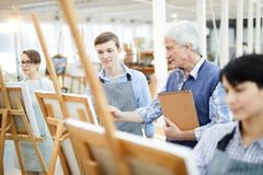 Portrait of Young art Student. Portrait of mature art teacher helping group of students painting picture on easels in art class, copy space royalty free stock photography