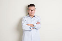 Portrait of mature Asian man arms crossed Stock Images