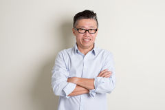 Portrait of mature Asian man arms crossed and smiling Stock Photography