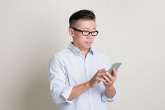 Portrait of mature Asian man using smartphone Stock Image