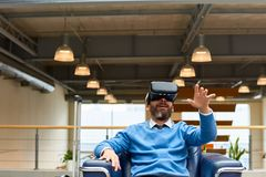 Mature Man Immersed in Virtual Reality. Portrait of mature bearded man wearing VR headset sitting in armchair looking amazed and excited reaching out with his Royalty Free Stock Photography