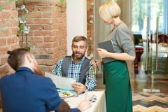 Young Waitress Taking Order in Cafe. Portrait of mature bearded men making order in cafe reading menu items to young pretty waitress during lunch break time Royalty Free Stock Photos