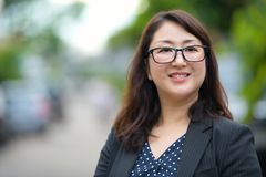 Mature happy beautiful Asian businesswoman smiling and thinking in the streets outdoors. Portrait of mature beautiful Asian businesswoman in the streets outdoors royalty free stock images