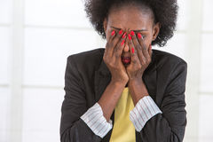 Portrait of mature black unhappy business woman at desk in office stock photography