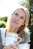 Portrait of mature blond woman drinking tea Stock Photos