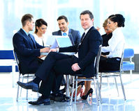 Portrait of mature business man smiling during meeting with colleagues Stock Photo
