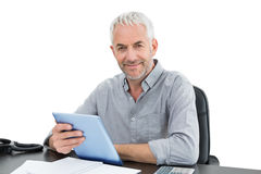 Portrait of a mature businessman with digital tablet at desk Royalty Free Stock Photography