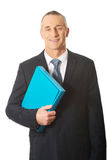 Portrait of mature businessman holding a binder Stock Photo