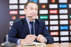 Mature Businessman at Press Conference. Portrait of mature businessman speaking to microphone at press conference, sitting against promo wall stock images