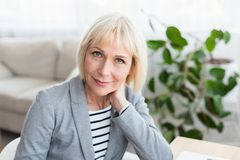 Portrait of mature businesswoman looking at camera. Working at home office stock photo