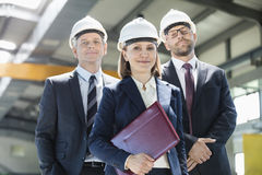 Portrait of mature businesswoman with male colleagues in metal industry royalty free stock image