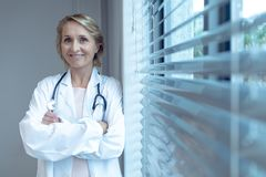 Female doctor standing with arms crossed in the hospital stock image