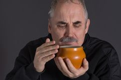 Caucasian man smelling earthenware pot with food against dark background Royalty Free Stock Images