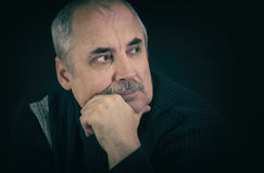 Portrait of mature Caucasian man thinking in darknes Stock Image